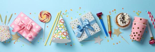 Contenitori di regalo e accessori di compleanno su fondo blu, vista superiore