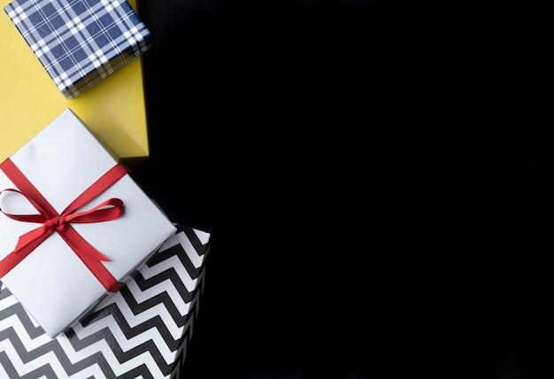 Scatole regalo su sfondo nero con copia spazio.