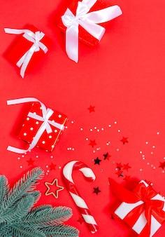 Scatole regalo, giocattoli di natale, rami di abete, stelle, bastoncini di caramello su fondo rosso. banner, modulo cartolina. copia spazio, piatto laici. capodanno, natale, vacanze, 2021 vista dall'alto orientamento orizzontale