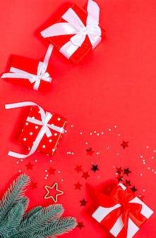 Scatole regalo, giocattoli di natale, rami di abete, stelle, su fondo rosso. banner, cartolina vuota. copia spazio, piatto laici. capodanno, natale, vacanze 2021 vista dall'alto