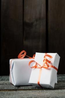 Scatole regalo sul tavolo di legno scuro. scatole bianche legate con un nastro rosso.