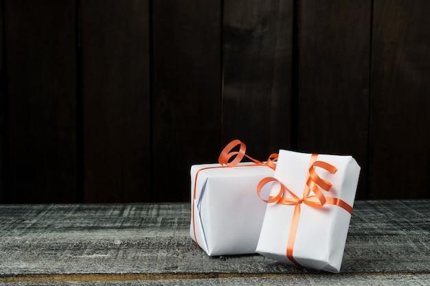 Scatole regalo sul tavolo in legno scuro con copia spazio. scatole bianche legate con un nastro rosso.