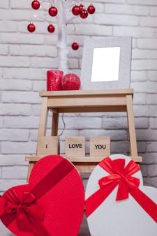Scatole regalo a forma di cuore e cornice vuota
