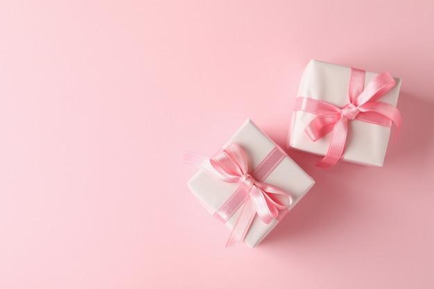 Scatole regalo su sfondo rosa, spazio per il testo