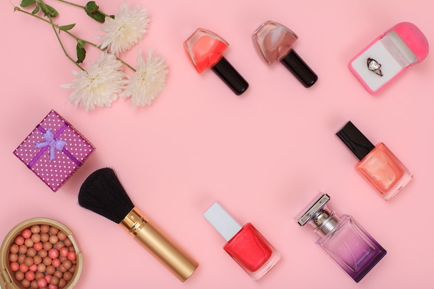 Confezioni regalo, polvere, smalto per unghie, bottiglia di profumo, pennello e fiori su sfondo rosa. cosmetici e accessori donna. vista dall'alto.