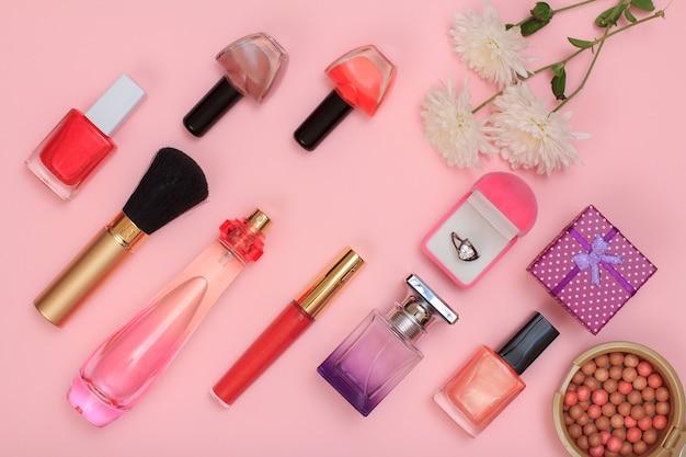 Confezioni regalo, polvere, smalto per unghie, bottiglia di profumo, rossetto, pennello e fiori su sfondo rosa. cosmetici e accessori donna. vista dall'alto.