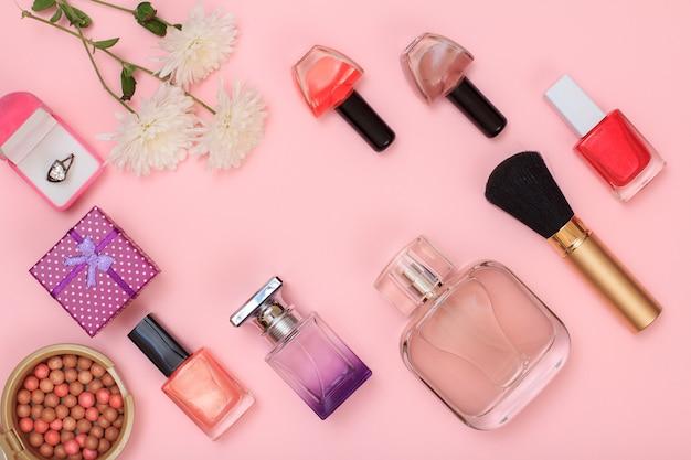 Confezioni regalo, polvere, smalto per unghie, bottiglia di profumo, rossetto, pennello e fiori su sfondo rosa. cosmetici da donna. vista dall'alto.