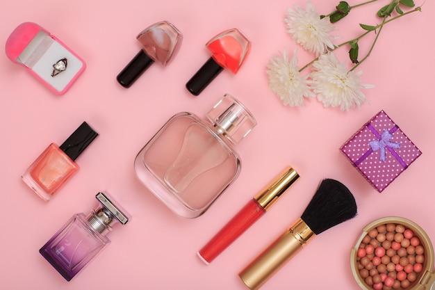 Scatole regalo, polvere, smalto per unghie, bottiglie di profumo, rossetto, pennello e fiori su uno sfondo rosa. cosmetici e accessori donna. vista dall'alto.