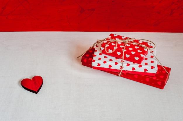 Scatole regalo e cuore rosso su fondo di legno rosso-bianco. regali per san valentino.