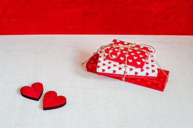 Contenitori di regalo e cuori rossi su fondo di legno rosso-bianco. regali per san valentino.