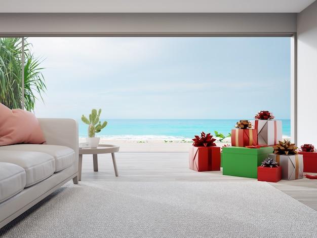 Confezioni regalo e divano sul pavimento di legno del luminoso soggiorno nella moderna casa sulla spiaggia