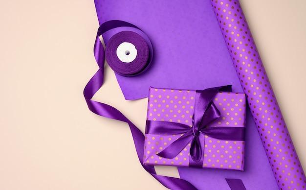 Scatole regalo legate con nastro di seta viola su fondo beige, vista dall'alto. sfondo festivo, piatto