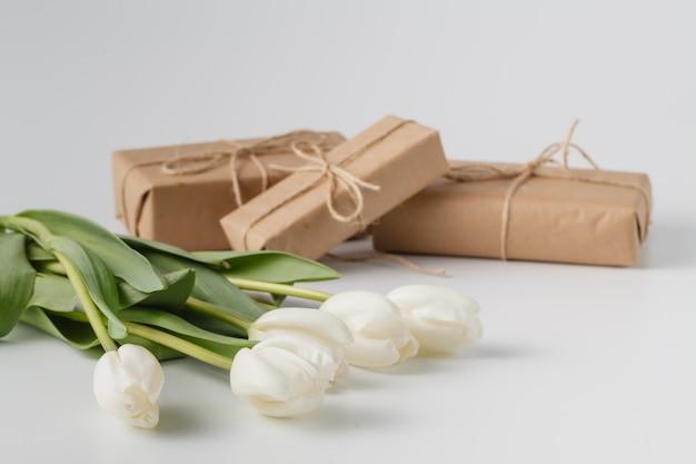 Mazzo dei contenitori e di tulipani di regalo su superficie bianca