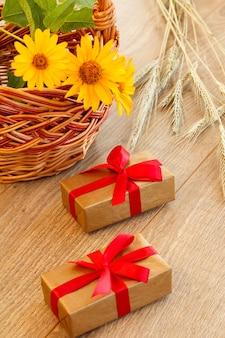 Confezioni regalo, cesto di vimini con fiori e spighette di grano su tavole di legno. vista dall'alto.