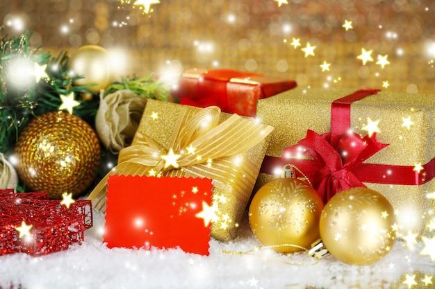 Scatole regalo con etichetta vuota e decorazioni natalizie sul tavolo su sfondo luminoso