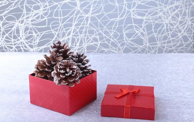 Scatole regalo con fiocco e palle di natale su legno.