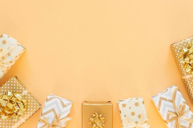 Scatole regalo con fiocchi su una vista dall'alto, piatta e dorata