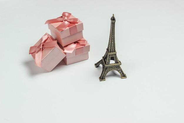 Scatole regalo con fiocchi e una statuetta della torre eiffel su sfondo bianco. shopping a parigi, souvenir