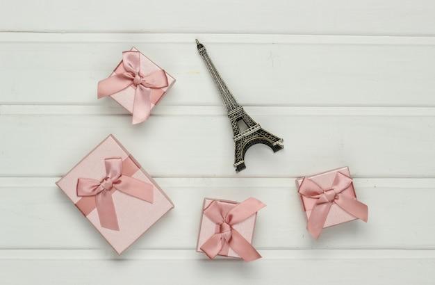 Scatole regalo con fiocchi e statuetta della torre eiffel sulla tavola di legno bianca. shopping a parigi, souvenir