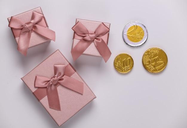 Scatole regalo con monete su bianco