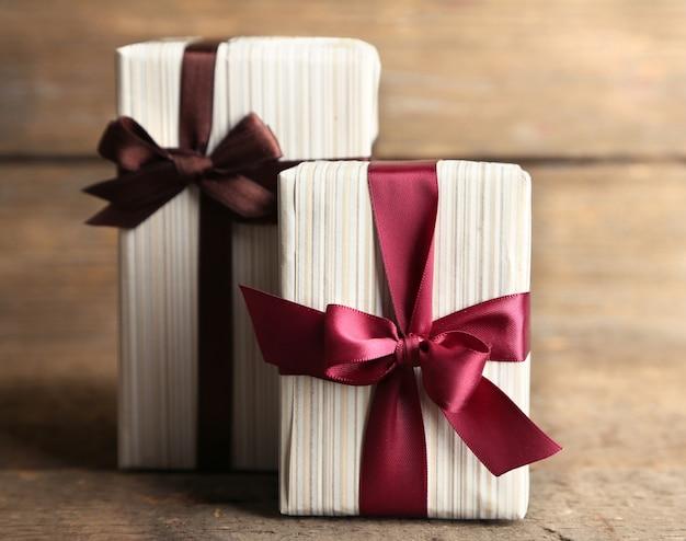 Scatole regalo con nastro colorato su superficie in legno