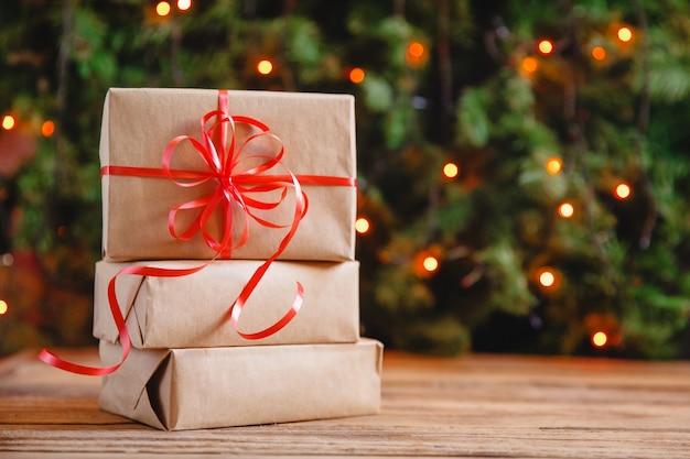 Scatole regalo con un grande fiocco rosso su uno sfondo bokeh di scintillanti luci di festa. regalo di natale.