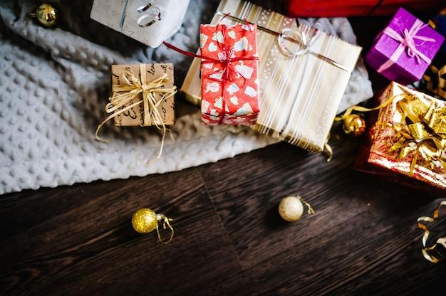 Scatole regalo con ornamenti in legno marrone, maglia grigia. spazio per testo, design. buone vacanze. vista dall'alto. laici piatta. regali avvolti alla moda. buon natale, concetto di nuovo anno. compleanno.