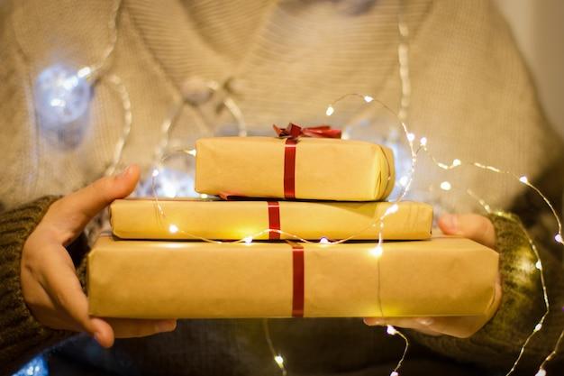Scatole regalo con nastro rosso nelle mani. le mani tengono regali in carta artigianale con ghirlanda luminosa