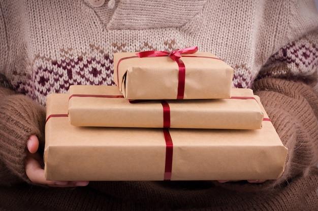 Scatole regalo con nastro rosso nelle mani. le mani tengono regali in carta artigianale