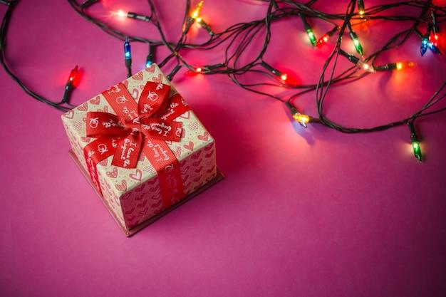 Scatole regalo con nastri rossi. sfondo di carta rosa. regali per natale o un compleanno.