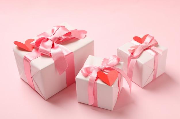 Scatole regalo con con cuori decorativi su sfondo rosa