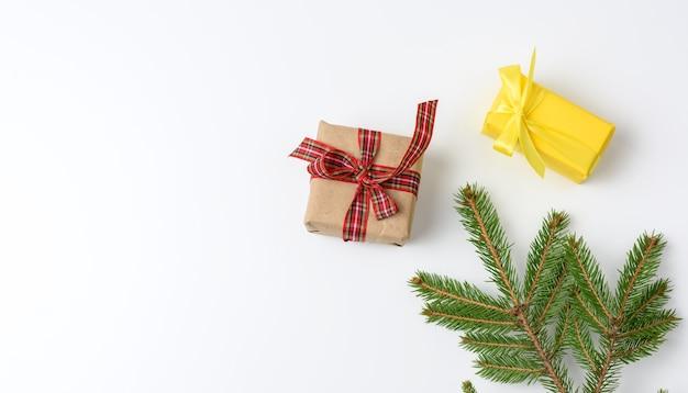 Scatole regalo avvolte in carta marrone e legate con un nastro su bianco, vista dall'alto, copia dello spazio