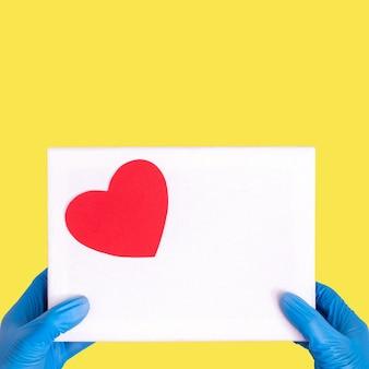Concetto di regalo durante la pandemia di coronavirus. scatola bianca o busta con cuore rosso