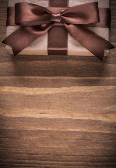 Contenitore regalo con fiocco marrone su tavola di legno d'epoca.