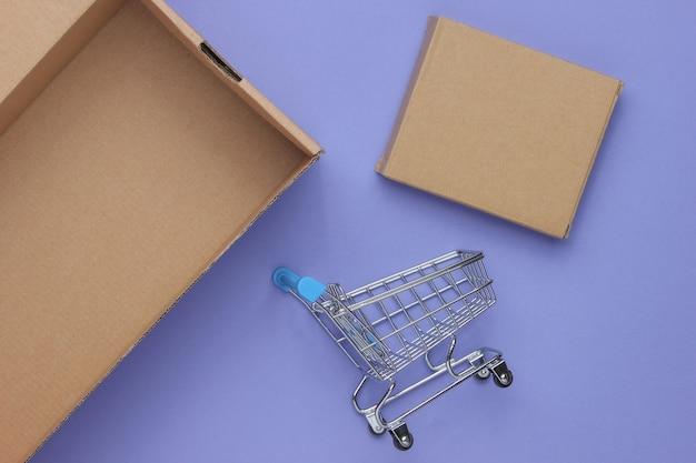 Concetto di consegna del regalo. scatole di cartone e mini carrello della spesa su sfondo viola.
