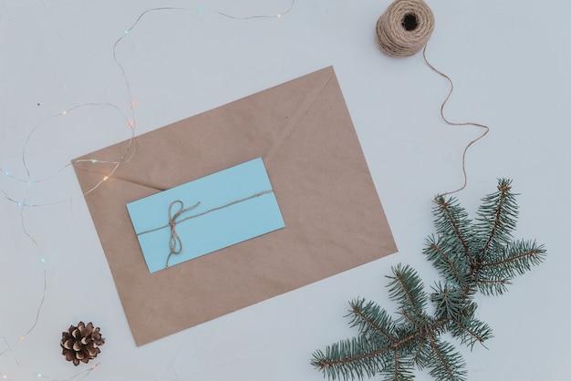 Busta regalo fatta di carta artigianale su uno sfondo di rami di abete lettera e busta fatta a mano per natale.