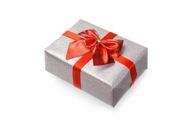 Il regalo nella confezione d'argento festosa è legato con un nastro rosso con un fiocco su un tavolo bianco, isolato.