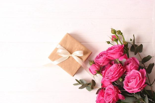 Regalo e fiori su una vacanza di sfondo colorato fanno un regalo congratulazioni