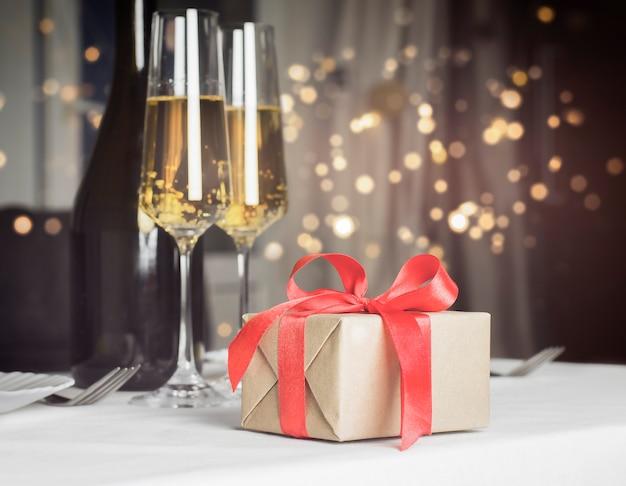 Regalo e bicchieri di champagne con luci sfocate a parete