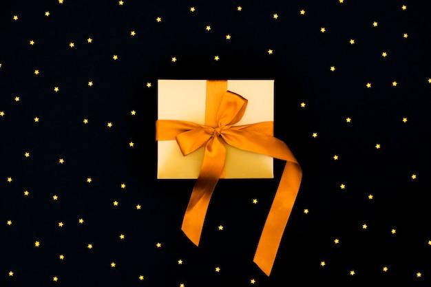 Scatola regalo in oro con fiocco in raso arancione su sfondo nero con tante piccole stelle.