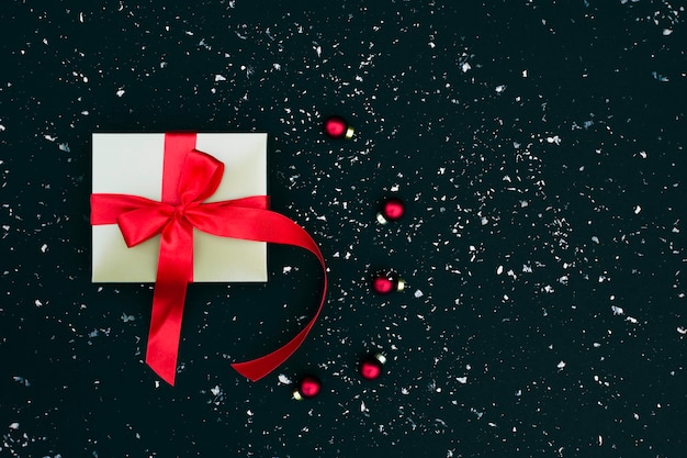 Confezione regalo in oro con fiocco in raso rosso su fondo nevoso nero
