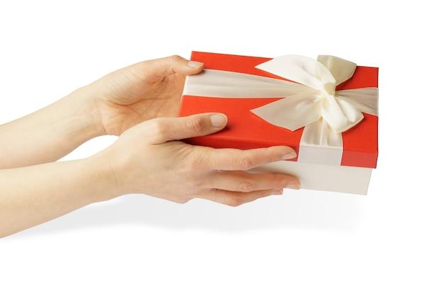Regalo in mani isolate. mani femminili che tengono una scatola rossa con un nastro bianco e un fiocco.