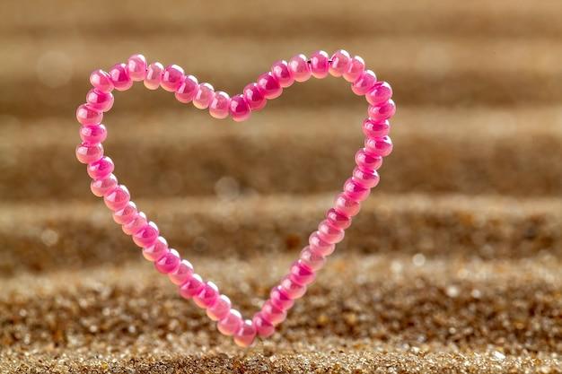 Perline a forma di cuore regalo su uno sfondo di sabbia.