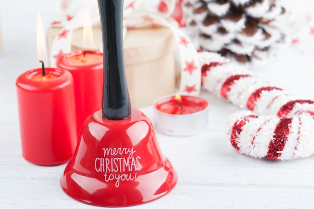 Regalo in scatola kraft con nastro di stelle rosse, candele accese e decorazioni