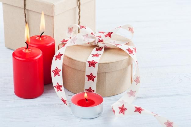 Regalo in scatola kraft con nastro di stelle rosse, candele accese e cuore