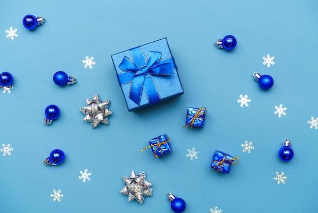 Banner scatola di carta regalo con fiocco in nastro blu e palle di natale blu scuro su sfondo blu con sno...
