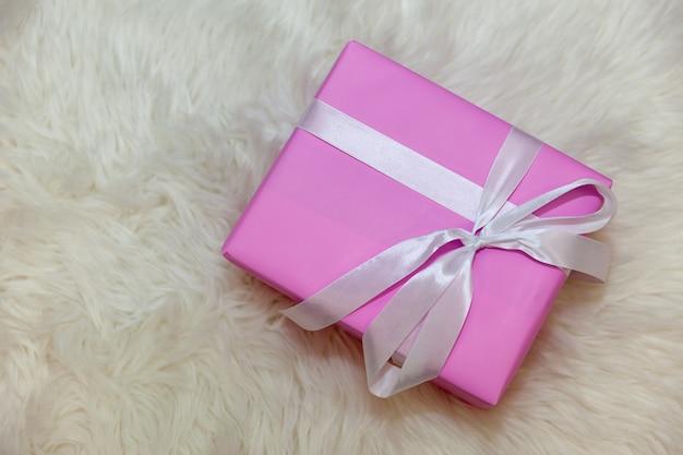 Regalo in confezione rosa su sfondo chiaro