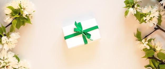 Disposizione bianca del piano del fondo del ramo del fiore di melo della scatola attuale del regalo. la molla floreale fiorisce il concetto verde del contenitore di regalo