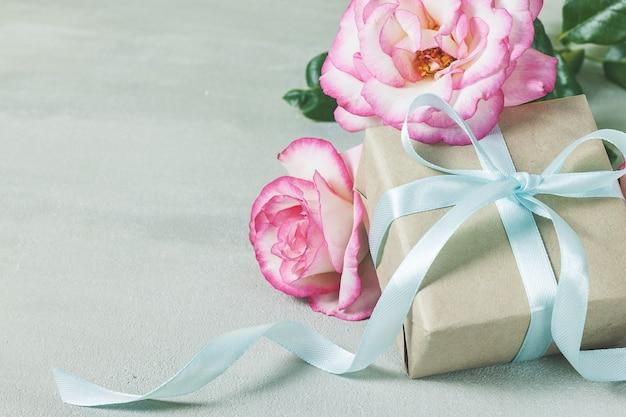 Confezione regalo o presente avvolto in carta artigianale e fiore rosa rosa sul tavolo grigio