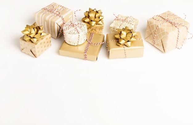 Regalo o regalo scatole d'oro e coriandoli di stelle sulla vista del piano d'appoggio bianco. composizione piatta per compleanno, natale o matrimonio.
